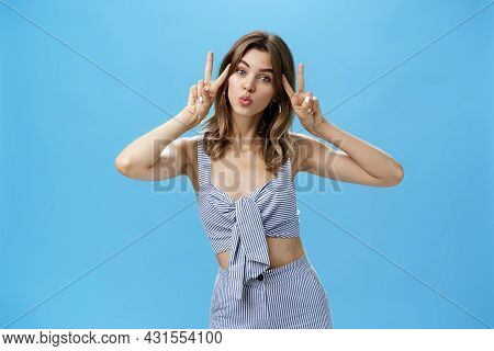 Charming Cute Unretouched Woman With Chestnut Hair And Tattoo Showing Peace Gestures Near Face Foldi