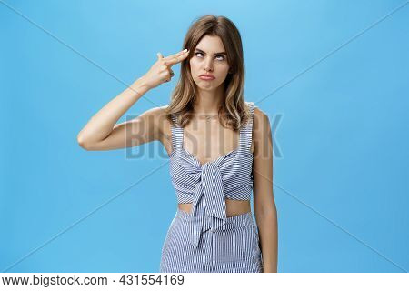 Funny And Attractive Young Charismatic Female Dying From Boredom Showing Gun Gesture Near Forehead R