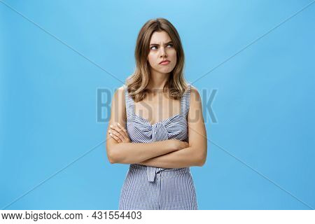 Studio Shot Of Woman Thinking Seriously Being And Hesitant Pursing Lips Holding Hands Crossed On Che