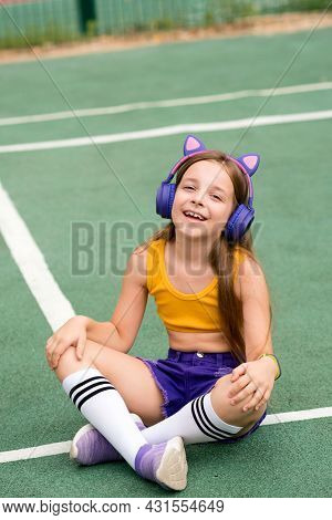 Relaxed Carefree Preteen Girl With Wireless Headphones Wears Trendy Clothes, Chilling On Sports Grou