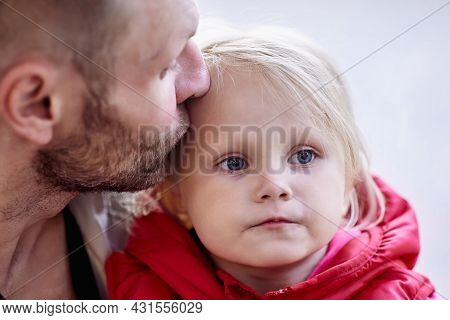 Caucasian Man Kisses Baby Daughter In Forehead.