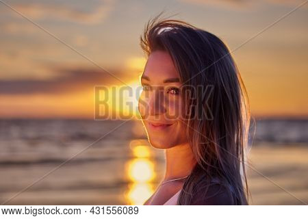 Portrait Of Happy White Woman On Seaside During Sunset.