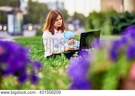 Woman Makes Remote Work With Baby On Knees In City Garden.