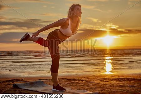 Yoga Training On Coast By Slim Woman During Sunset.
