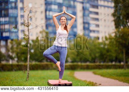Happy Woman Makes Yoga Training On Park Bench.