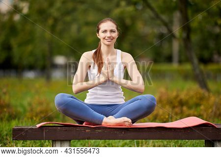 Smiling Woman On Park Bench Makes Yoga Exercises.