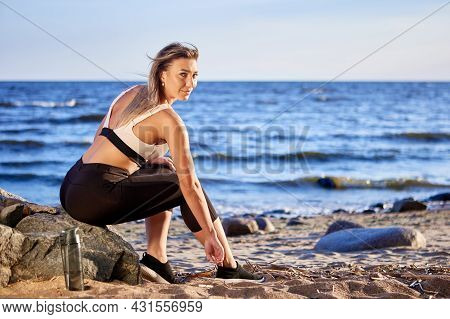 Woman Is Sitting Near Coast As Rest During Running.