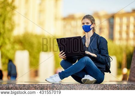Woman In Protective Medical Mask With Laptop Works Outdoors.