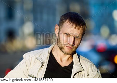 Portrait Of Frowning White Man With Stubble On Face.
