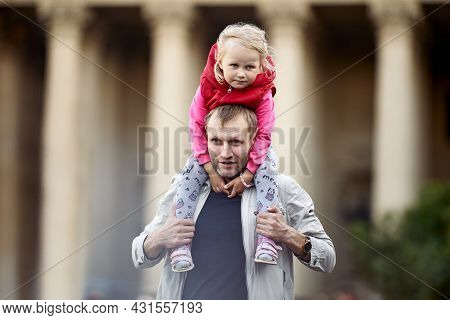 Toddler Girl Sits On Shoulders Of Father Outdoors.