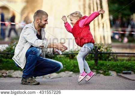 Happy Toddler Girl Plays With Father In Park Near Fountain.