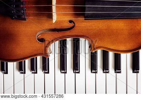 Violin on top of piano keyboard background with copy space for music concept