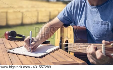 Musician guitarist songwriter playing acoustic guitar and writing music