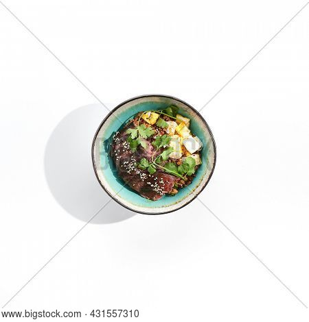Traditional oriental food - fried rice with egg and beef. Stir-fry rice in asian style on white background. Meat and rice with omelette in bowl. Isolated on white background