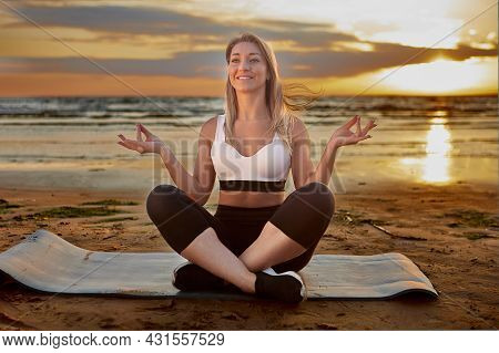 Yoga Training During Sunset By Happy Woman On Beach.