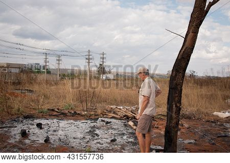 Man From The Environment Inspecting The Remains Of A Brush Fire At An Illegal Trash Dump In Granja D