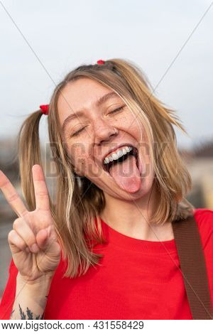 Vertical Portrait Of Young Blonde Woman With Freckles On Her Face And Two Funny Ponytails, Playfully