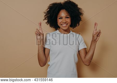 Young Hopeful African American Female Isolated On Beige Studio Background Crossing Fingers And Makin