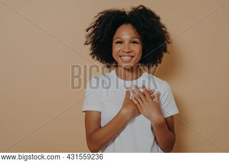 Gratitude Concept. Happy Thankful Young African Woman Isolated On Yellow Studio Background Holding H