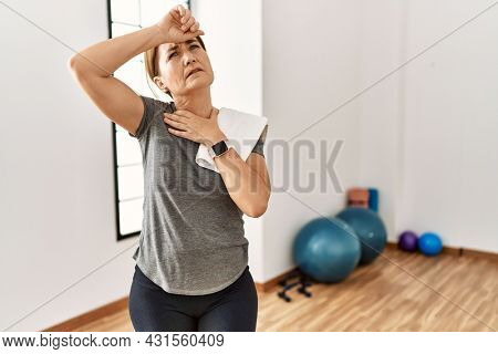 Middle age woman wearing sporty look training at the gym room touching forehead for illness and fever, flu and cold, virus sick