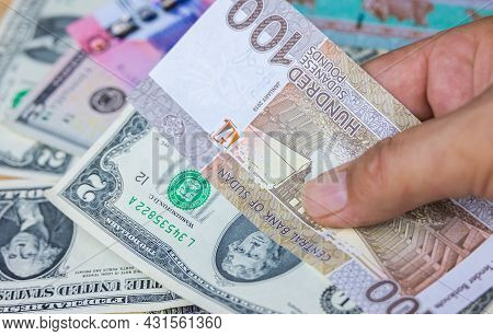 Male Hand Hold100 Sudanese Pounds Banknote With Us Dollars, The Currency Of Sudan. Close Up Paper Mo