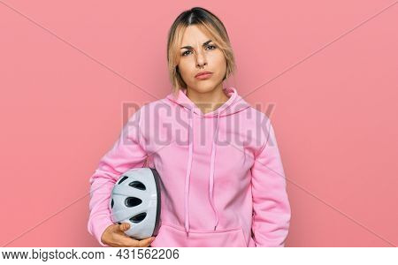 Young caucasian woman holding bike helmet thinking attitude and sober expression looking self confident