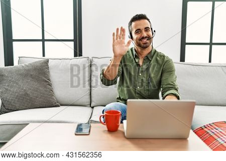 Young hispanic man with beard wearing call center agent headset working from home waiving saying hello happy and smiling, friendly welcome gesture