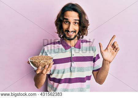 Young hispanic man holding lentils bowl smiling happy pointing with hand and finger to the side