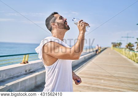 Hispanic sports man wearing workout style drinking water to stay hydrated outdoors on a sunny day