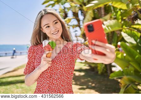 Young chinese girl eating ice cream make selfie by the smartphone at the promenade.