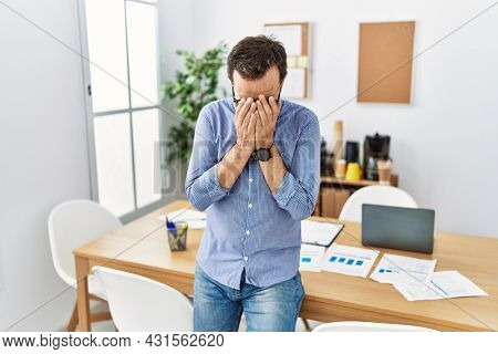 Middle age hispanic man with beard wearing business clothes at the office with sad expression covering face with hands while crying. depression concept.