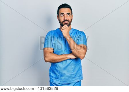 Handsome hispanic man with beard wearing blue male nurse uniform with hand on chin thinking about question, pensive expression. smiling with thoughtful face. doubt concept.