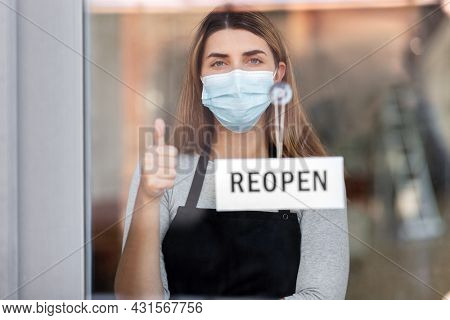 small business, reopening and service concept - woman in mask with reopen banner on window or door glass showing thumbs up