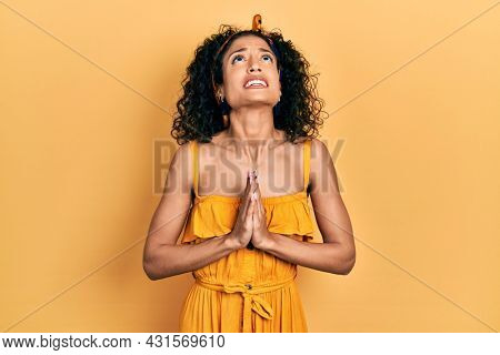 Young latin girl wearing summer dress begging and praying with hands together with hope expression on face very emotional and worried. begging.
