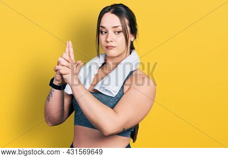 Young hispanic girl wearing sportswear and towel holding symbolic gun with hand gesture, playing killing shooting weapons, angry face