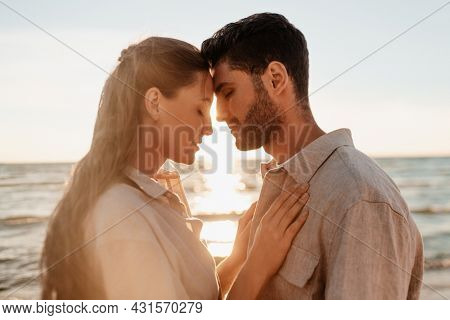 leisure, relationships and people concept - happy couple with closed eyes on summer beach