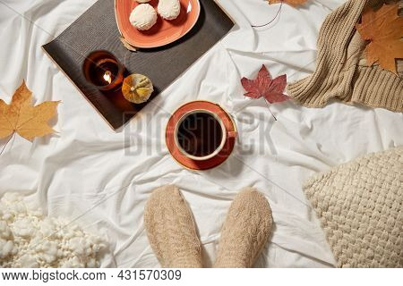 season and leisure concept - cup of coffee, feet in warm socks, autumn leaves and candle in bed at home