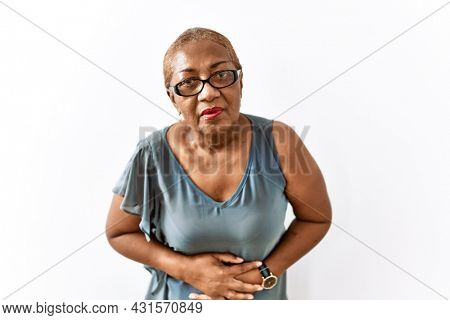 Mature hispanic woman wearing glasses standing over isolated background with hand on stomach because indigestion, painful illness feeling unwell. ache concept.