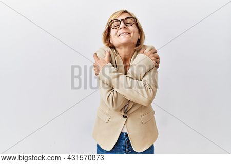 Middle age blonde business woman standing over isolated background hugging oneself happy and positive, smiling confident. self love and self care
