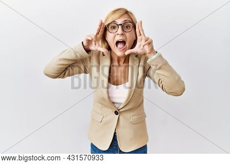 Middle age blonde business woman standing over isolated background smiling cheerful playing peek a boo with hands showing face. surprised and exited