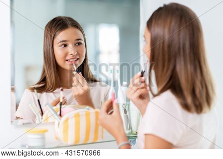 beauty, make up and cosmetics concept - teenage girl applying lip gloss and looking to mirror at home bathroom