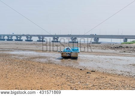 Pyeongteak, South Korea; August 11, 2021: Small Outboard Fishing Boat Stranded On Muddy Beach At Low