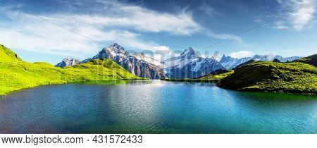 Panorama of Bachalpsee lake in Swiss Alps mountains. Snowy peaks of Wetterhorn, Mittelhorn and Rosenhorn on background. Grindelwald valley, Switzerland. Landscape photography