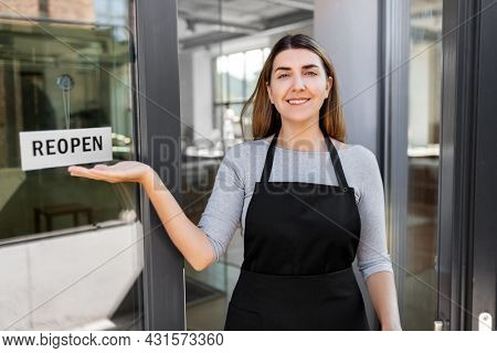 small business, reopening and service concept - happy smiling woman showing reopen banner on window or door glass