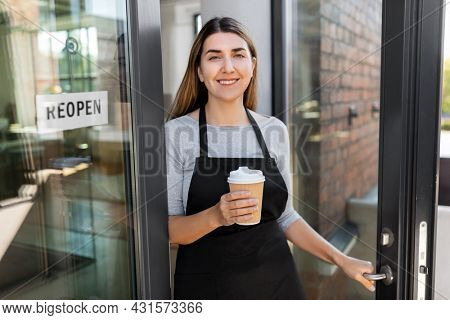 small business, reopening and service concept - happy smiling woman with takeaway coffee cup and reopen banner on window or door glass