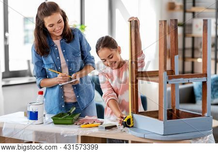 family, diy and home improvement concept - happy smiling mother and daughter with ruler measuring old wooden table for renovation at home