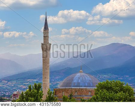Minaret Of The Mosque And The Trees On The Background Of The Sky. And Hills. Selective Focus