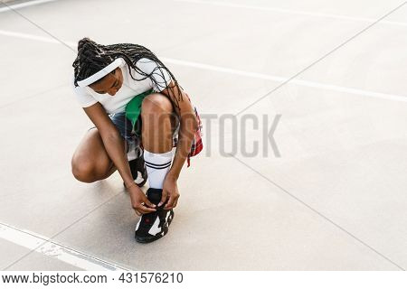 Happy young african woman in casual outfit tying shoelace at a seafront promenade embankment wearing wireless headphones