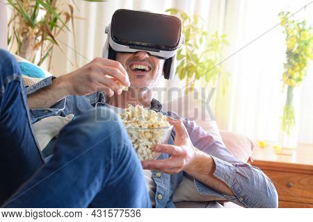 Man Watching Multimedia Content In Virtual Reality Glasses Eating Popcorn Lying On The Sofa At Home