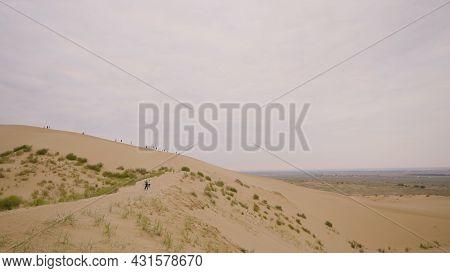 People Walk Along Sandy Ridge. Action. Tourists Walk On Sand Hills In Desert. Walking Tour In Desert
